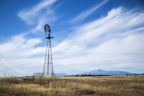 Tall windmill in bare land